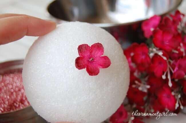 Blume mit einer Nadel in Syroporbällen stechen