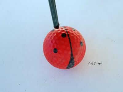 Schwarze Punkte auf einen Golfball malen