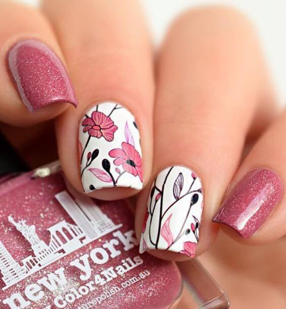 Glänzende rosane Nägel mit Blumenmuster