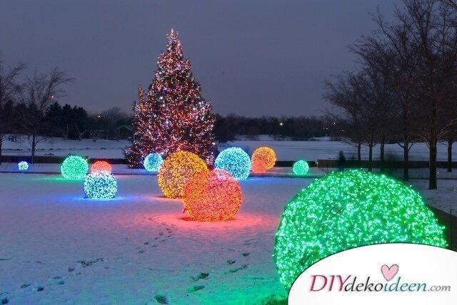 leuchtende Weihnachtskugeln basteln, mit Lichterketten als Gartendeko