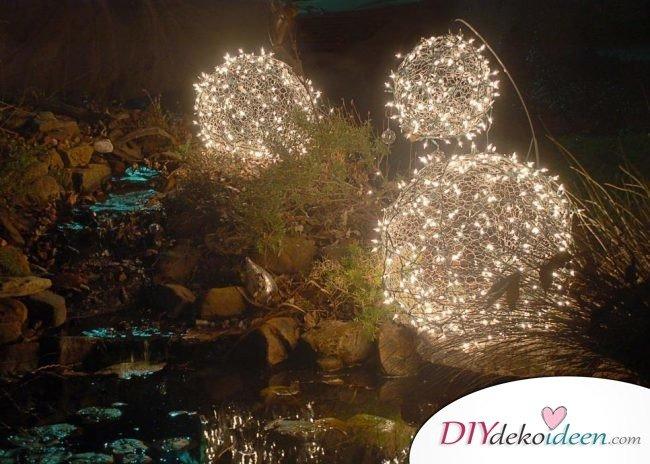 Weihnachtsdeko Ideen mit Lichterketten-leuchtende Kugeln für den Garten