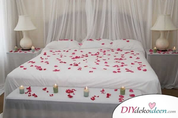 DIY Schlafzimmer Deko-Ideen zum Valentinstag: dezente Deko mit Kerzen und pinken Rosenblättern