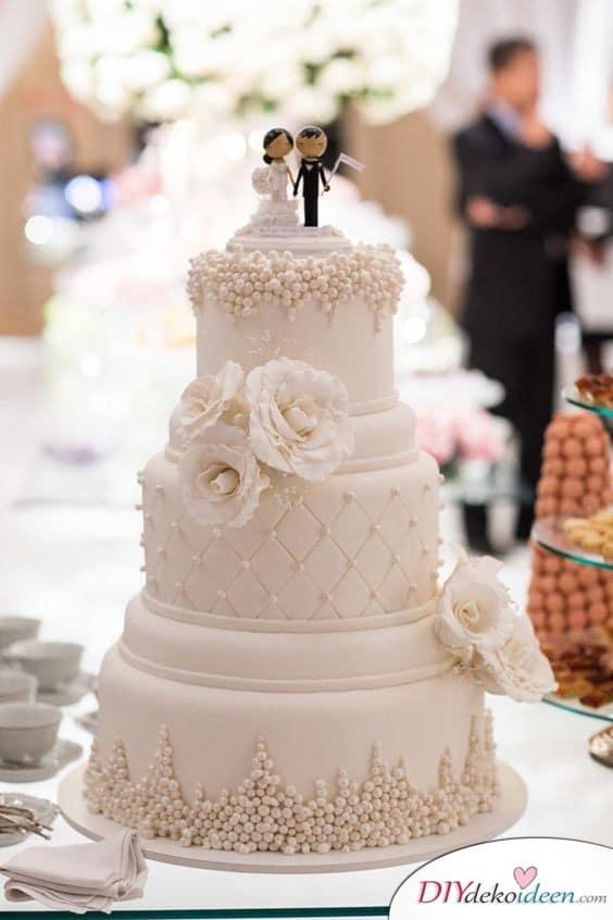 Torte mit Hochzeitstortenfiguren und Zuckerperlen