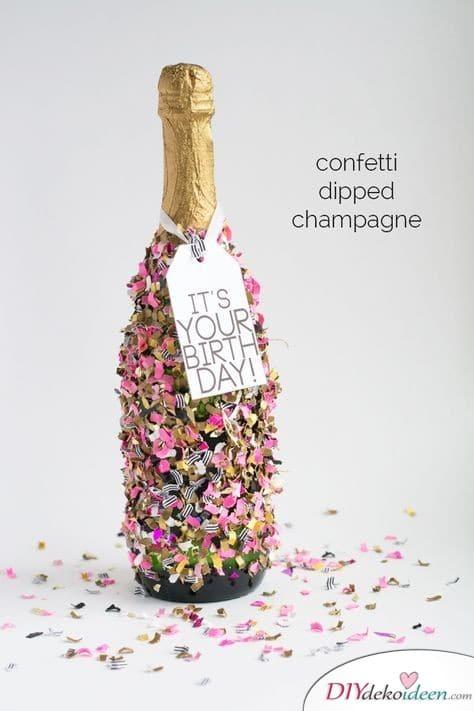 Mit Konfetti beklebte Champagnerflasche als Geburtstagsgeschenk